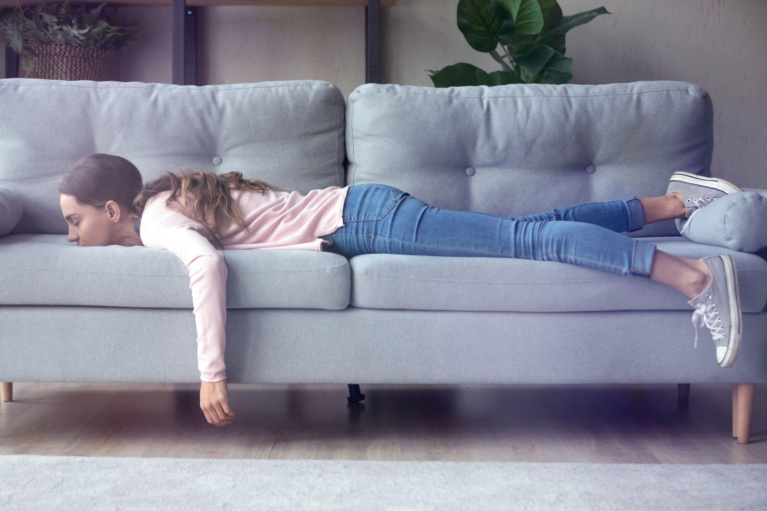 Eine junge Frau, die erschöpft auf einem Sofa liegt