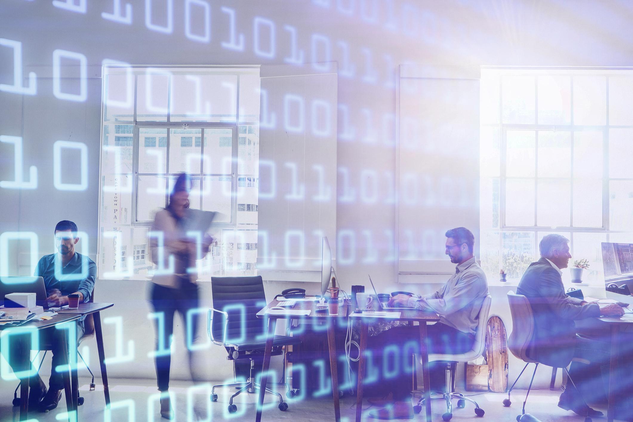 Ein Büro, in demiten mehrere Personen an Computern arbeiten
